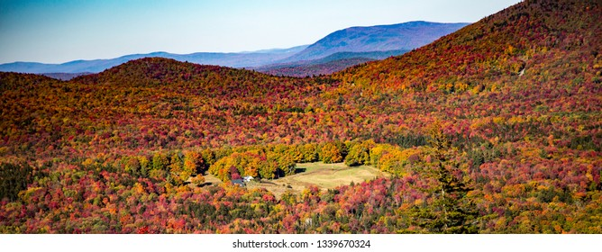 A small farm surrounded by trees in vibrant fall color near Mt Snow, Vermont