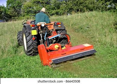 Small farm tractor bush hogging on a grass field in Trentino Alto Adige. Italy