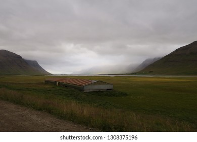 Small farmland in misty mountain valley, in Westfjords Iceland