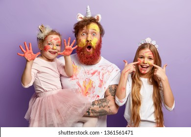 Small female child shows hands soiled with colourful gouache paintings, her glad sister has stains of watercolour on face, stunned father stares at camera, have fun before mother returns from work.