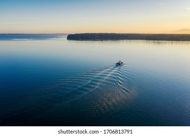 Small Ferry Boat In Route to the Mainland During a Beautiful Sunrise. On a calm spring morning the Lummi Island ferry boat motors over to Gooseberry Point on the Lummi Indian Reservation.