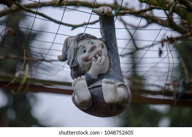 A small figure made of clay, is hanging down, only held by his hand in a metal fence