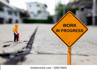 small figure of a man digging concrete street with Work in Progress message.