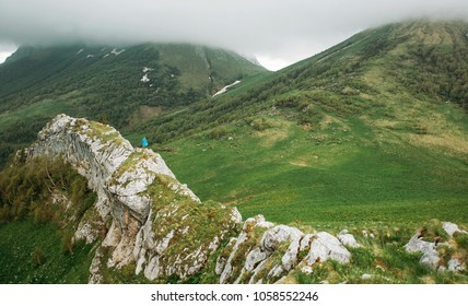 Small figure of traveler in raincoat walking on cliff wall among mountains in summer in rainy weather.