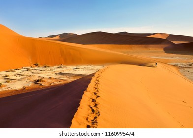Small figure walking on the desert dunes on the sunny day during sunset, Deadvlei, Sossusvlei, Namibia, Africa