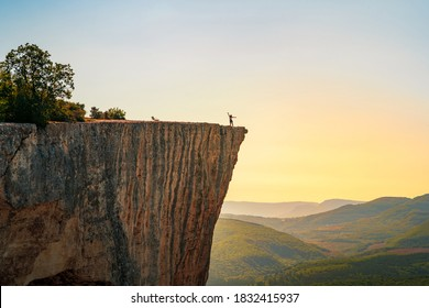 A small figure of a woman tourist with open arms, standing on the edge of a cliff in the summer mountains. The concept of a small man in the midst of a powerful nature.