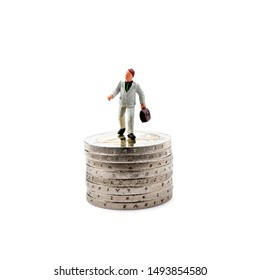 Small figurine and coins isolated on white background. Save money and accumulate wealth. Taxes and social issues.