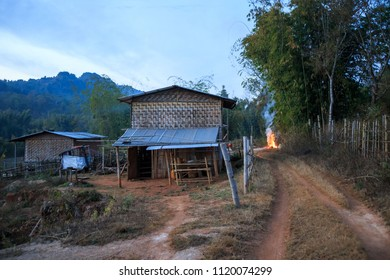 Small fire burns down dirt road next to traditional wooden home in rural Myanmar village