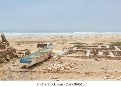 small fishery boat and remaining foundation of the stone house beside the beach of arabian sea in mahrah region, yemen