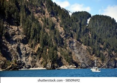 Small fishing boat in Alaska near a cliff