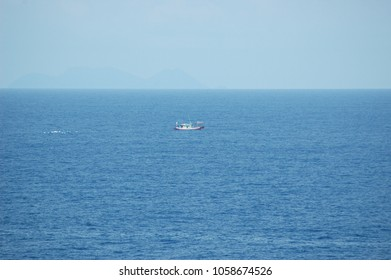 A small fishing boat being followed by a flock of seagulls. The boat looks small on the vastness of the ocean. A rocky island is rising from the horizon. The sky is clear blue.