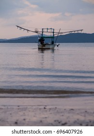 Small fishing boat in a calm and peaceful ocean during dusk time