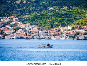small fishing boat crossing the blue waters opposite the beautiful island of Spetses, located in Saronikos gulf near Athens city, Greece