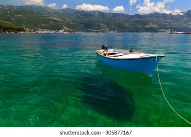 Small fishing boat is moored at the coast in transparent water Adriatic Sea