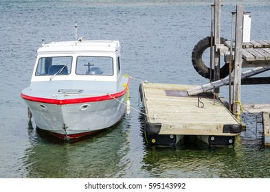 Small fishing boat moored at a old weathered wooden dock