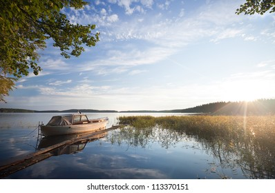 Small fishing boat moored on Saimaa lake in Imatra town, Finland