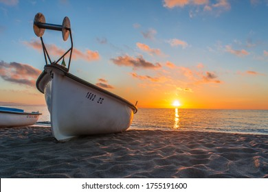 Small fishing boat on beach at sunset.