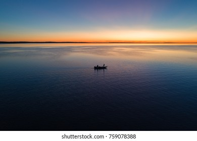 A small fishing boat on Houghton Lake in Michigan at sunrise