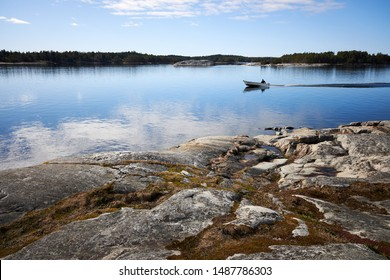 Small fishing boat on still sea water. Beautiful rocks on the shore of th Baltic Sea in Kasnäs, Kemiö island in Finland.