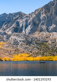 A small fishing boat sailing on the beautiful Convict Lake on a sunny autumn day in Northern California. Blue water with some reflection from bright yellow trees at the bottom of Laurel Mountain.