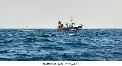 Small fishing boat sailing in an open Mediterranean sea, close-up. A view from the yacht. Leisure activity, sport and recreation, food industry, traditional craft, environmental damage concepts