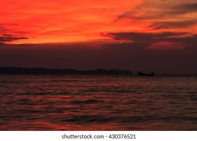 A small fishing boat in the sea on cloudy day and colorful sunset sky.