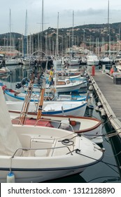 Small fishing boats and small boats moored along the pier of the port of Varazze (Italy). On the moored yatch background