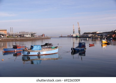 Small fishing boats in Port of Sunderland on the River Wear cast their reflection on to the still waters