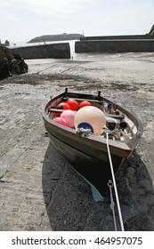 A small fishing craft pulled up on the hard of a harbour in a small village in Cornwall