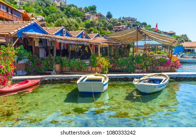 The small fishing harbor with old boats next to the scenic patio of the coastal restaurant, decorated with bright flowers in pots, Kalekoy, Kekova, Turkey.