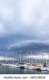 Small fishing and recriational boats docked in the Port of Cagliari, Sardinia, Italy. Overcast cloudy sky on the background