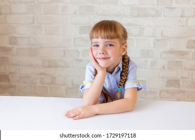 A small five-year-old girl of European appearance looks thoughtfully at the camera, smiles, holds her cheek with her hand