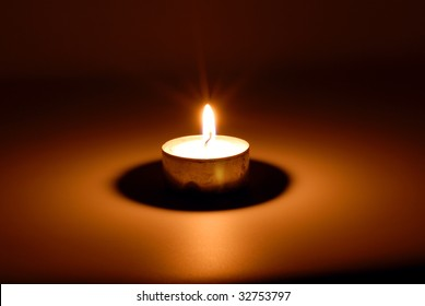 Small flame of a burning candle in darkness