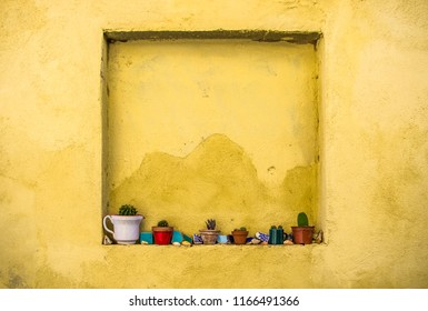 small flower pots with succulents and with colorful mosaic pieces in wall window niche with yellow mexican style cornwall