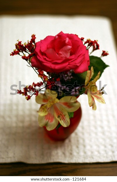 A small flower vase with a rose and assorted other flowers.