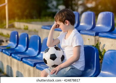 Small football fans disappointed after the loss goal by his favorite team