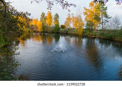 A small fountain in the middle of the pond in the early autumn with trees growing on the shore. With already yellowed on some and still green on other foliage.