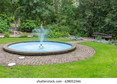 Small fountain and pool in a park with grass and trees around it