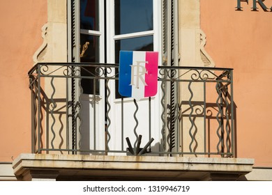 Small french flag hanging on a blacony in St Tropez