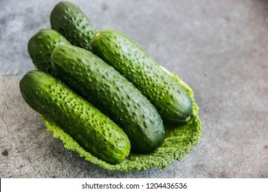 Small fresh cucumbers on cabbage leaf