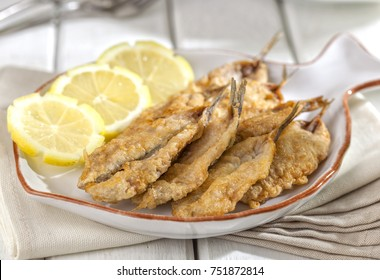 Small fried fish appetizer served with lemon