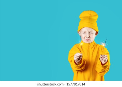 a small frightened child in a yellow hat and jacket holds burning sparklers in his hands on a blue background
