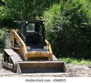 A small front end loader working a load of gravel