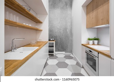 Small, functional kitchen with wooden countertop and hexagonal floor tiles