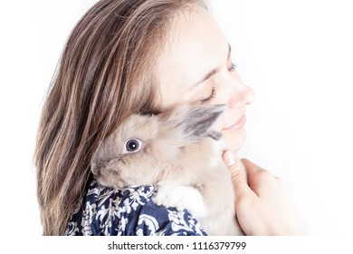 small, funny Dutch decorative rabbit sits on the shoulder of a loving and caring hostess (isolated on white background)