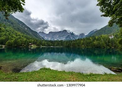 The small Fusine Lake (Lago di Fusine) and the Julian Alps, Mount Mangart, Tarvisio, Friuli Venezia Giulia, Italy, Europe