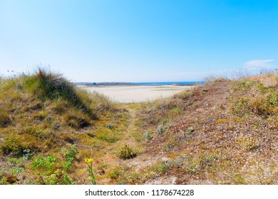 A small gap leads from grass and wildflower covered mounds to Plage Sainte-Marguerite and the blue Celtic Sea
