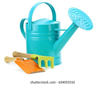 Small garden watering can, shovel and rake on a white background
