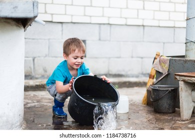 a small gardeners. rural life. outdoor games. children's pranks. happy childhood.visiting grandmother. city children in the village.little boy with a big bucket. the water is pouring out of the bucket