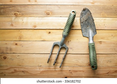 Small gardening shovel and fork on wooden background.